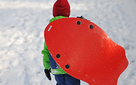 A child tobogganing in the snow