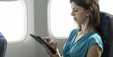 Woman using tablet on an airplane